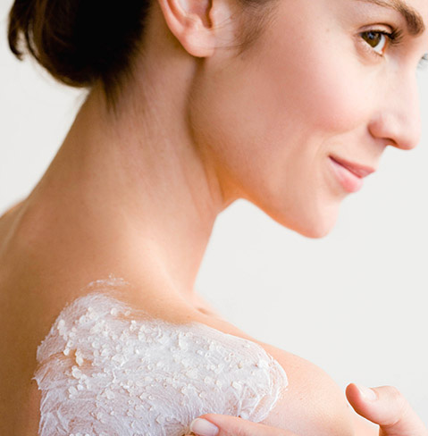 Back of a woman with fair skin who has some kind of cream on the back of her right shoulder right.