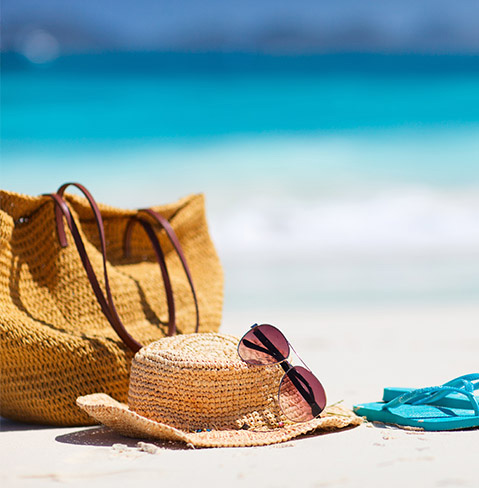 Beach bag, straw hat, purple sunglasses and turquoise sandals on a beach.